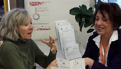 Bibliotecaria parla con utente presso il banco informazioni