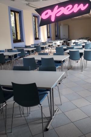 Foto della sala di consultazione, venti tavoli con piano bianco, quattro sedie con seduta azzurra per tavolo. con sedie