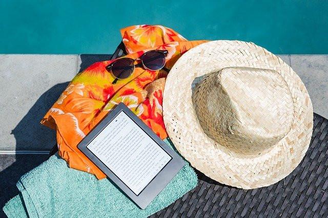 Cappello, lettore ebook e asciugamano a bordo piscina, foto
